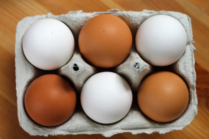 a six pack of white and brown eggs