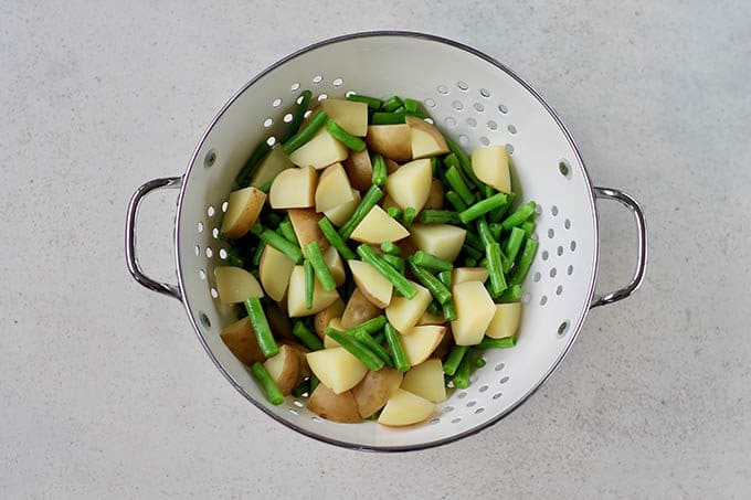 potatoes and green beans in a white colander