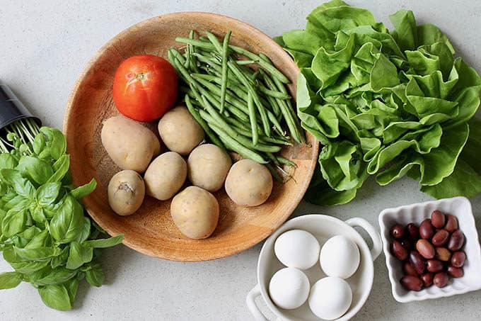 potatoes, basil, green beans, eggs, olives, tomato, lettuce on a grey background