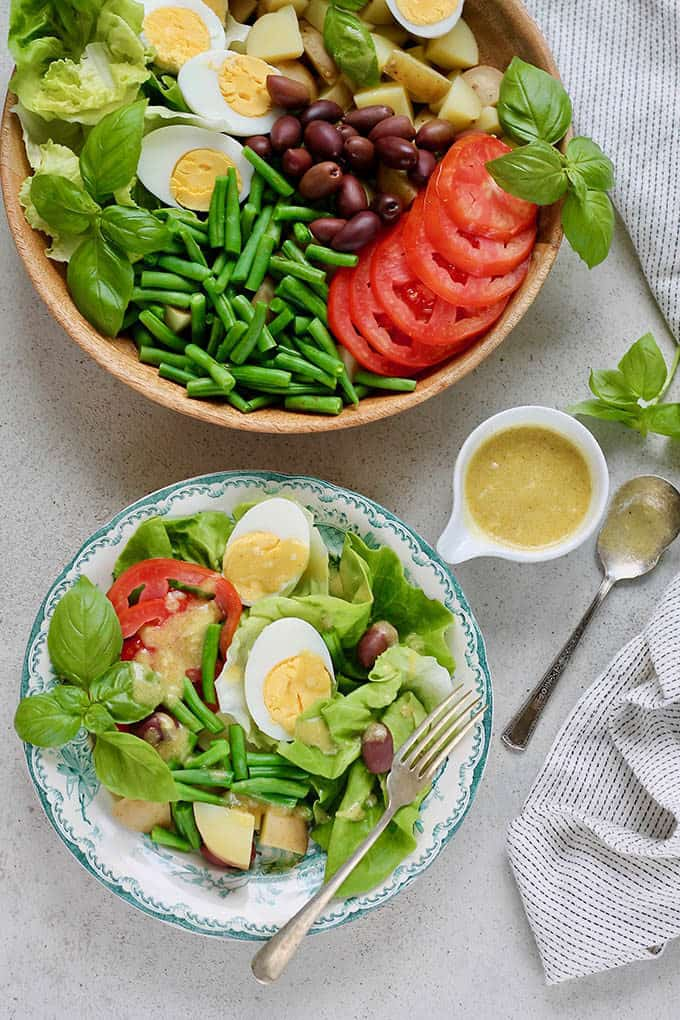 overhead photo of vegetarian niçoise salad on a grey background with a pot of salad dressing to the side