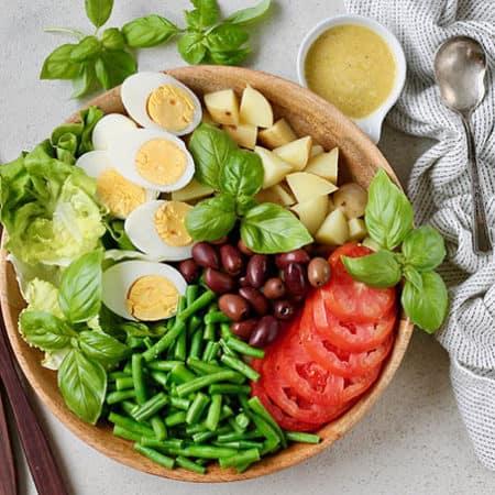 vegetarian nicoise salad on a wooden platter