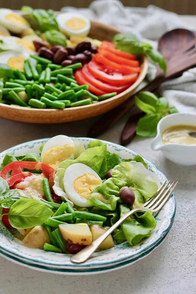 vegetarian niçoise salad on a blue and white plate with a wooden platter in the background