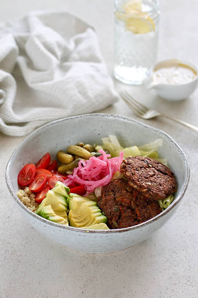 veggie burger bowl in a blue bowl topped with avocado, pickled onions, lettuce, and tomatoes