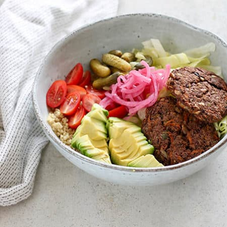 veggie burger bowl in a blue bowl with a white tea towel and silver fork to the side