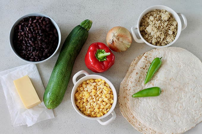 cheese, beans, zucchini, corn, pepper, onion, jalapeno, quinoa, and tortillas on a grey background