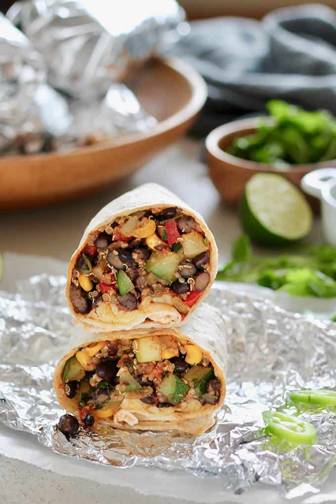 vegetarian black bean burrito on a piece of foil with foil-wrapped burritos in the background