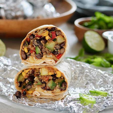 A stacked black bean freezer burrito on a piece of foil