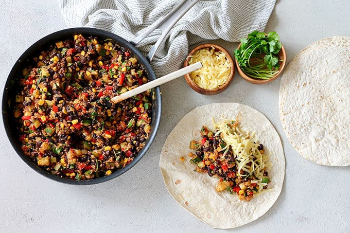 a pan of vegetarian burrito filling being spooned onto a wheat tortilla