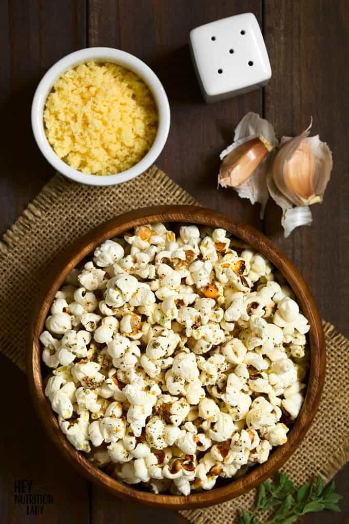 a wooden bowl of popcorn with garlic and nutritional yeast in the background