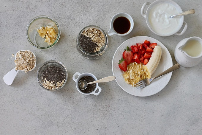 mashed banana and strawberries on a white plate, jars with oats and chia seeds, and plain yoghurt on a grey background