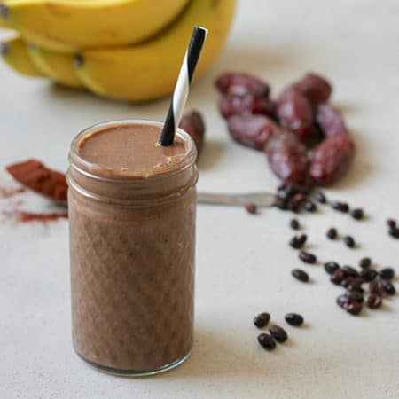 chocolate smoothie with bananas, dates, black beans, and cocoa powder in the background
