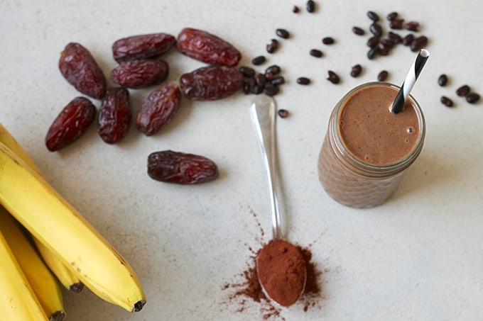 chocolate smoothie with bananas, beans, dates, and cocoa shot overhead on a grey background