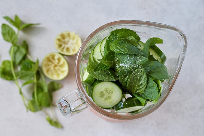 Ice, cucumber, mint, lime, and honey in a blender with juiced limes and mint in the background
