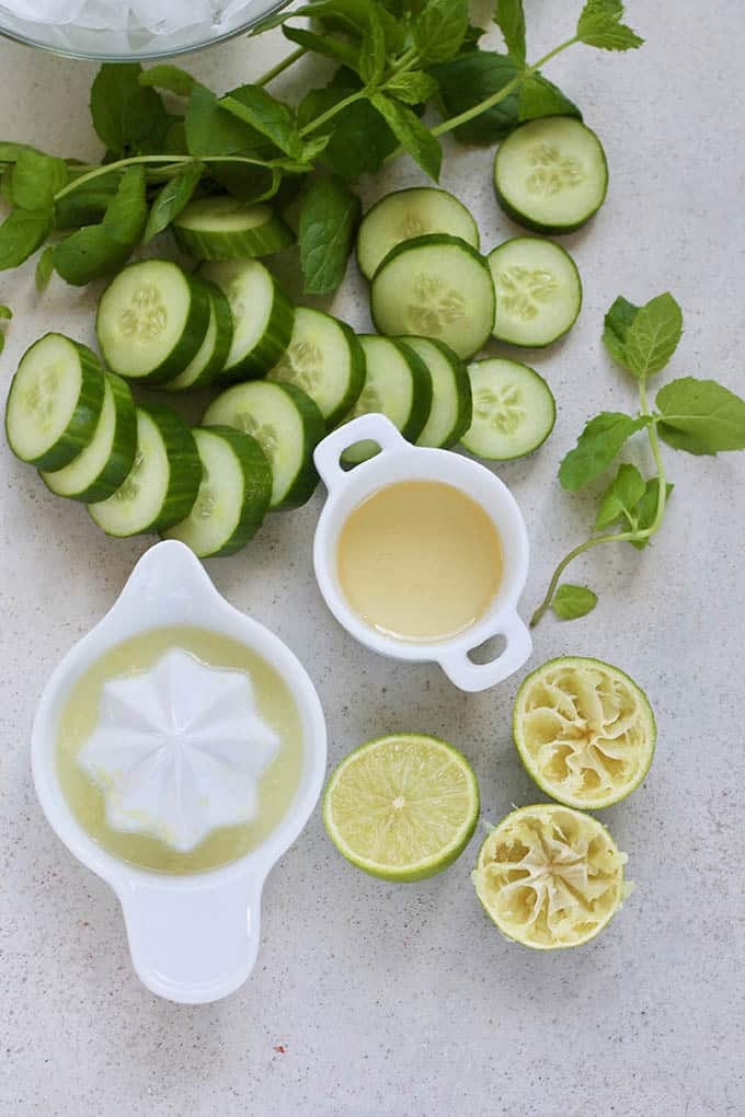 sliced cucumbers, mint, juiced limes, and honey on a grey background