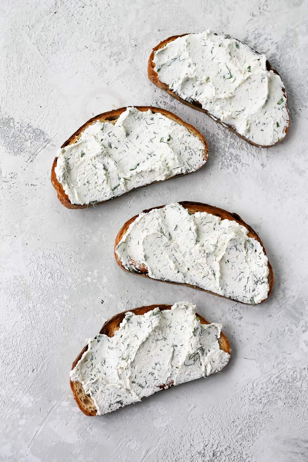 four slices of toast topped with herbed ricotta on a grey background