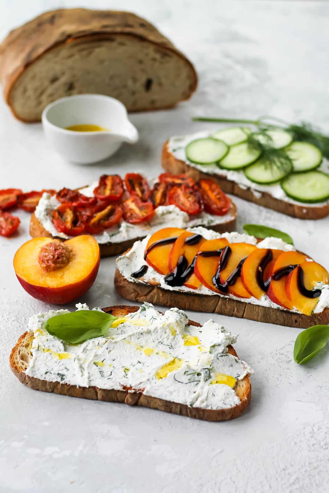 four slices of ricotta toast topped with fruits and vegetables with a loaf of sourdough bread in the background