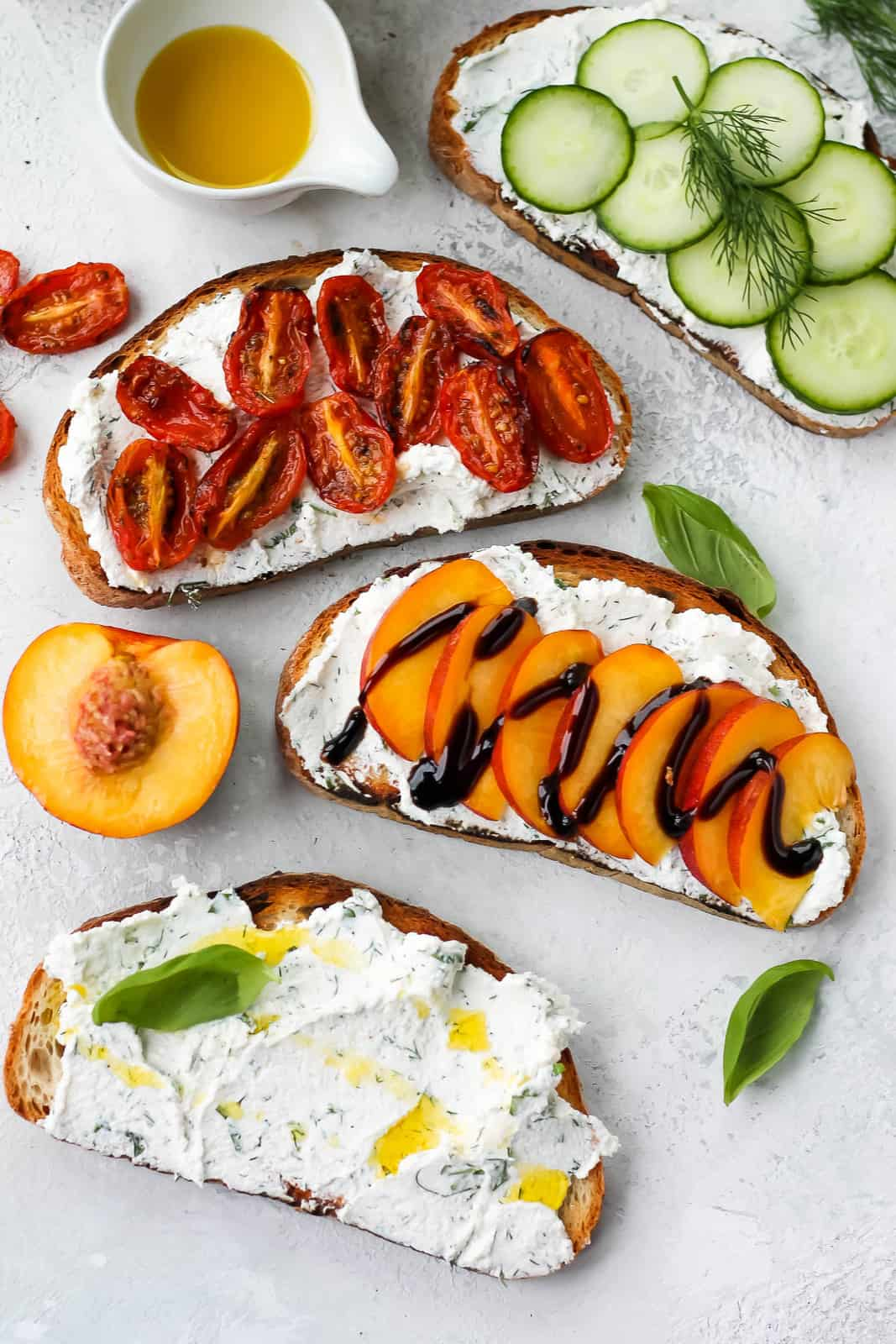 overhead photo of herbed ricotta toast topped with sliced peaches, roasted tomatoes, and cucumbers