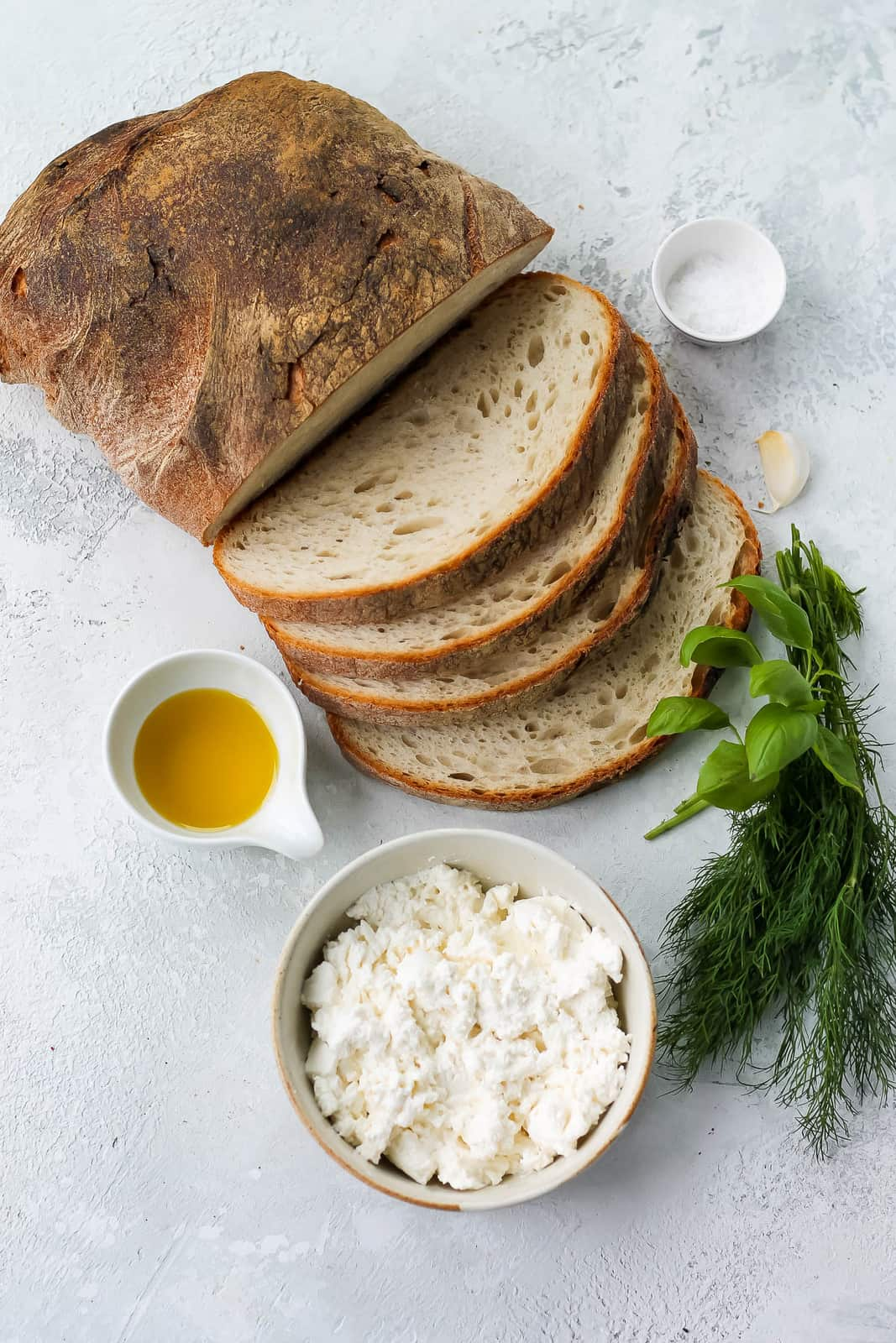 a loaf of sliced sourdough, a bowl of ricotta, some fresh herbs, olive oil, and salt on a grey background