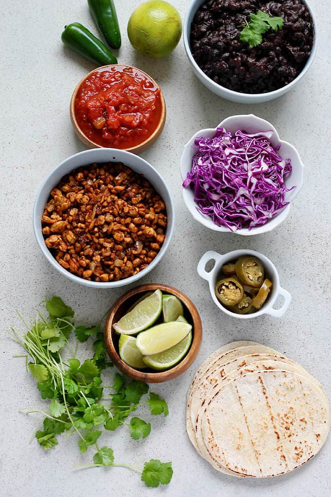 tempeh taco meat, tortillas, red cabbage, limes, cilantro, and black beans on a grey background
