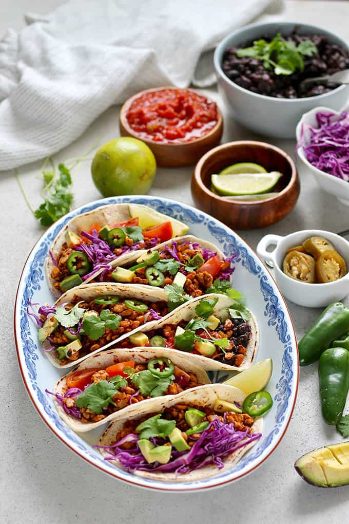 tempeh tacos on a blue platter with jalapenos, limes, and salsa in the background