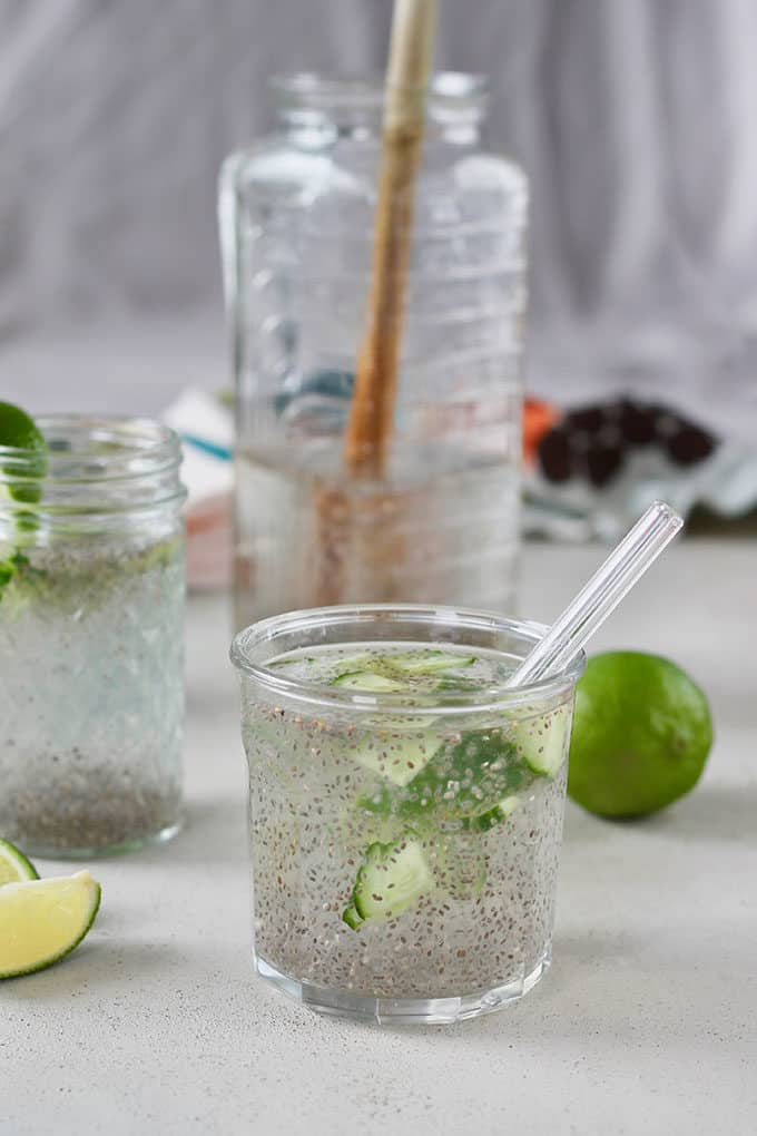 A glass of chia fresca with lime and cucumber and a glass straw, with a jug of chia fresca in the background