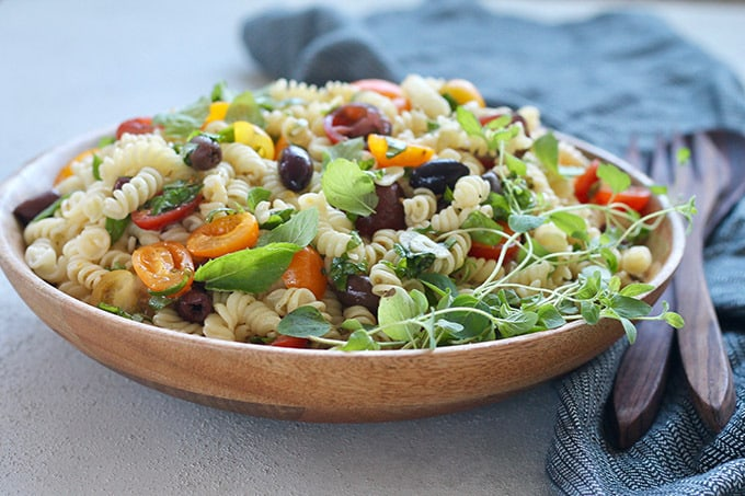 Summer pasta dish with olives, tomatoes, and herbs in a wooden bowl