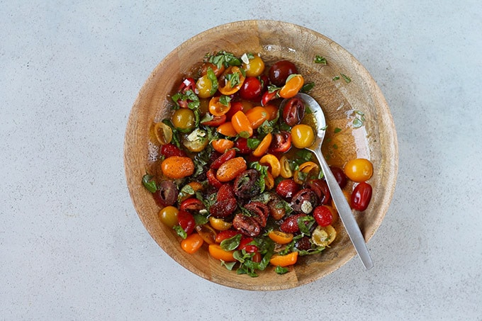 crushed tomatoes in a bowl with herbs and olive oil