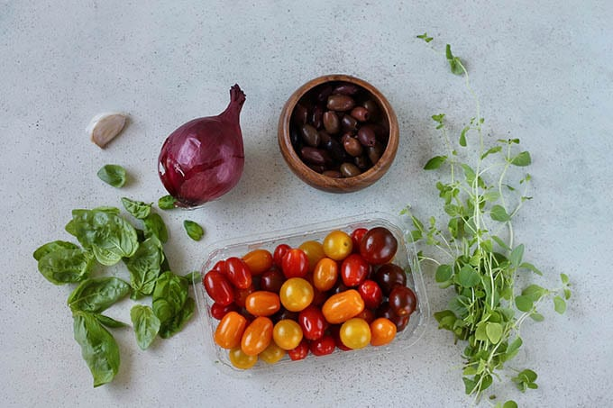 Tomates, herbs, onion, garlic, olives on a grey background