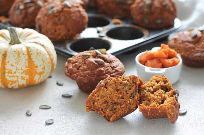 a healthy pumpkin muffin cut in half with pumpkin puree and a tray of muffins in the background