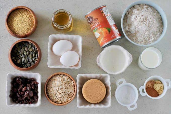 canned pumpkin, flour, yogurt, sugar, eggs, oats, millet, pumpkin seeds, raisins, and spices on a grey background