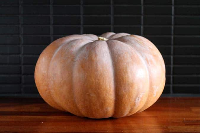 a cinderella pumpkin on a wooden counter top