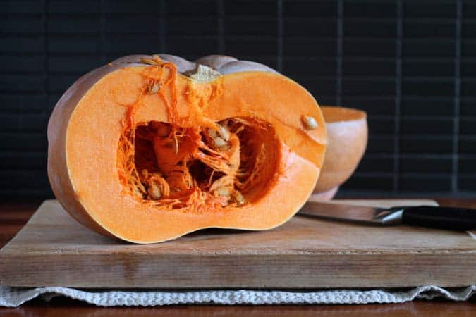 A pumpkin cut in half on a wooden cutting board