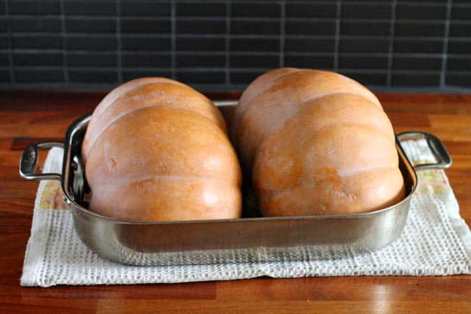 two pumpkin halves in a roasting pan