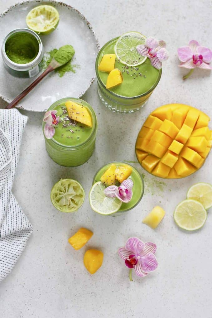 overhead photo of matcha green tea smoothies with lime slices and orchid blossoms scattered about