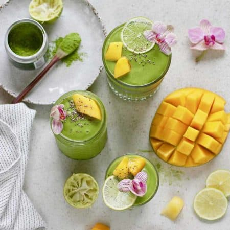 matcha green tea smoothies on a grey surface with a cut mango and matcha powder