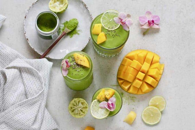 matcha green tea smoothies on a grey surface with a cut mango and matcha powder