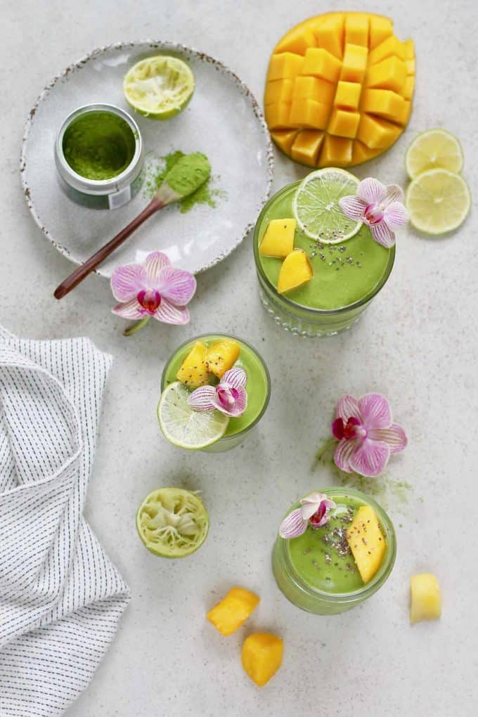 three glasses of matcha green tea smoothie garnished with mango, lime, and purple flowers