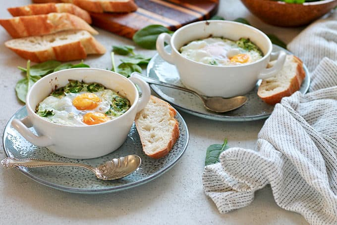 white ramekins with ricotta and spinach egg bake on blue plates with a baguette