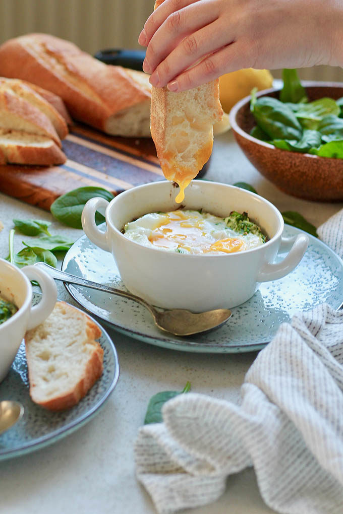 A slice of bread being dipped into a ricotta and spinach egg bake