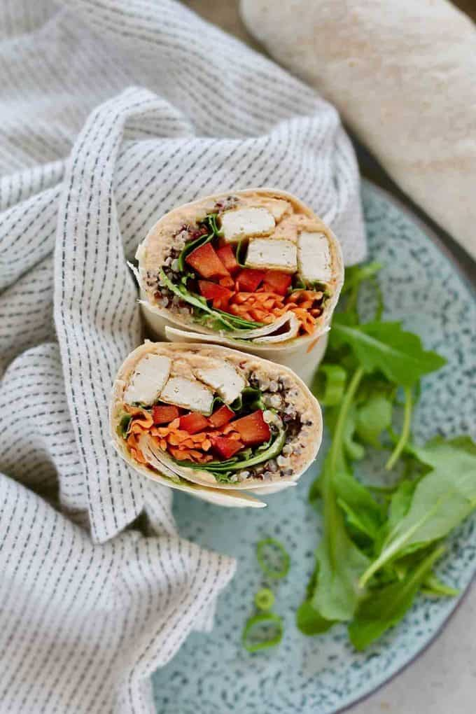 a spicy vegan wrap cut in half on a plate with a handful of greens on the side