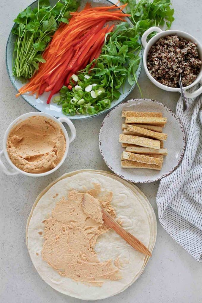 spicy hummus spread on a tortilla and a plate of vegan wrap fillings to the side