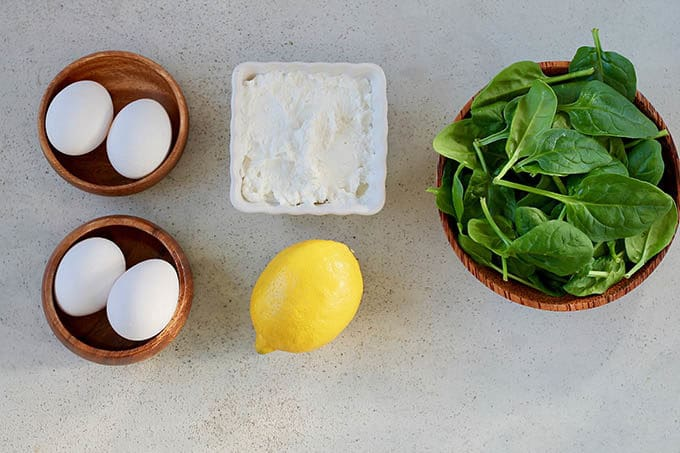 eggs, ricotta, a lemon, and a bowl of spinach on a grey background