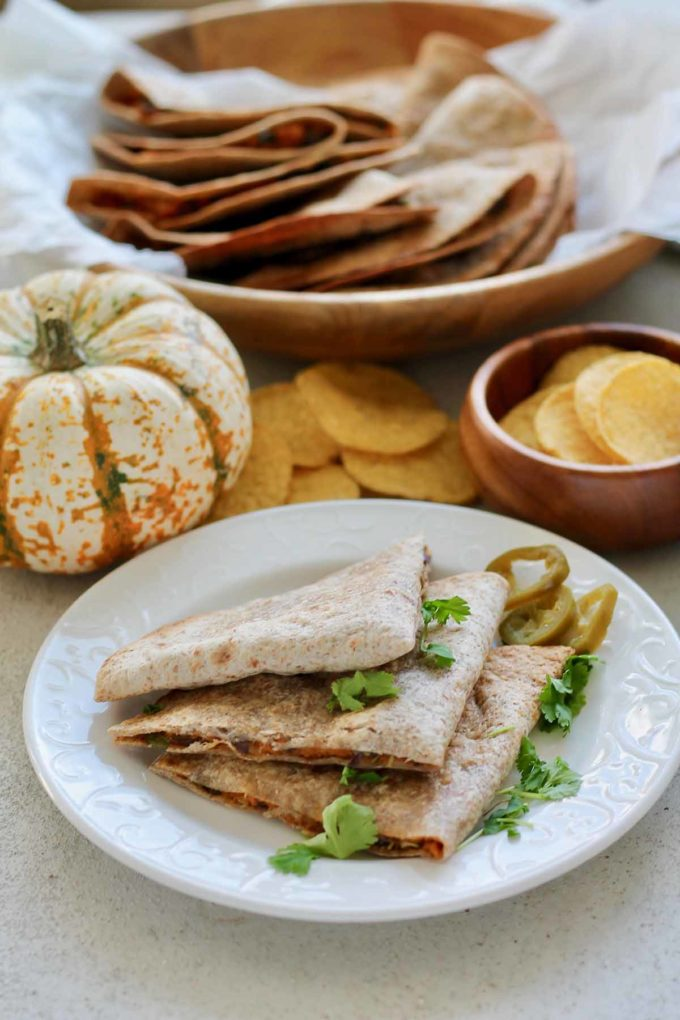 vegetarian quesadillas on a white plate with pumpkin in the background