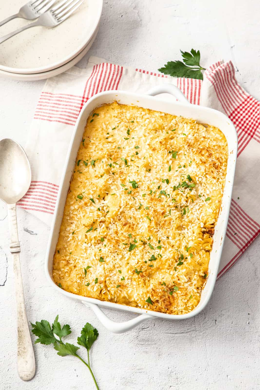 overhead photo of cheesy cauliflower pasta bake in a white casserole dish