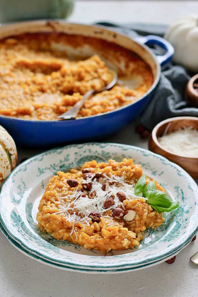 A plate of baked pumpkin risotto with a blue casserole dish of risotto in the background
