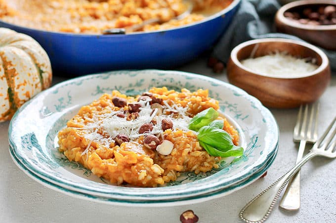 Baked brown rice pumpkin risotto on two blue and white plates