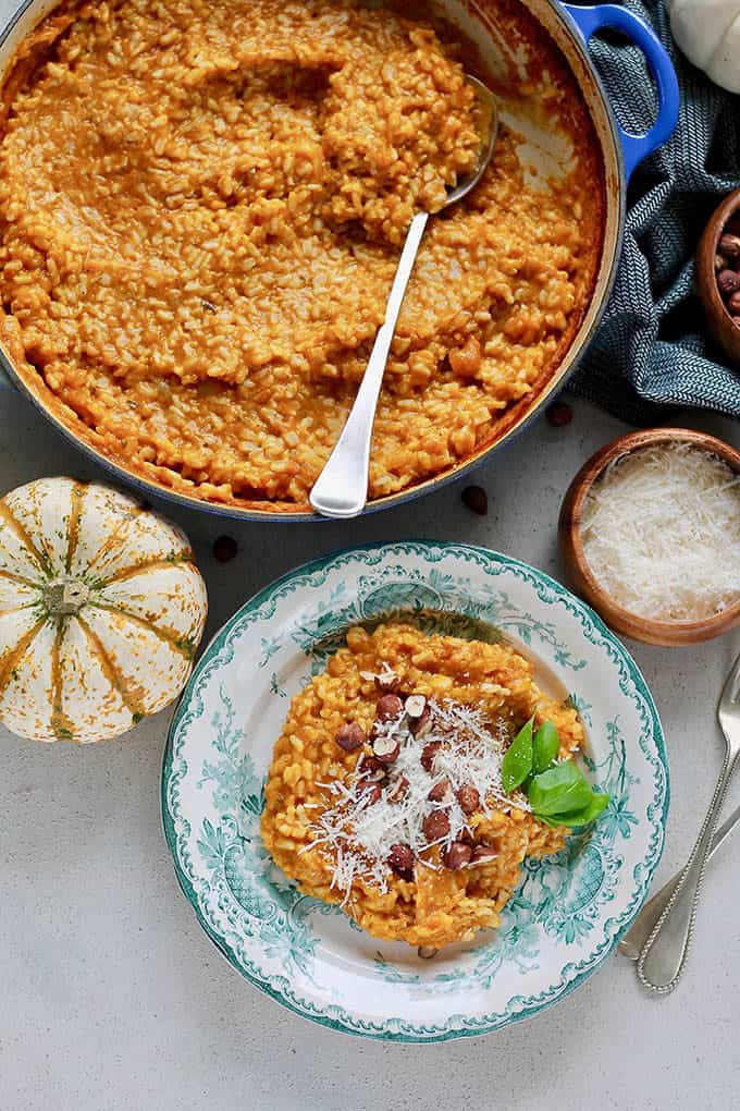 baked pumpkin risotto on a blue plate with a decorative pumpkin to the side