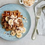 overhead photo of vegan banana waffles on a blue plate with a silver fork and white tea towel to the side