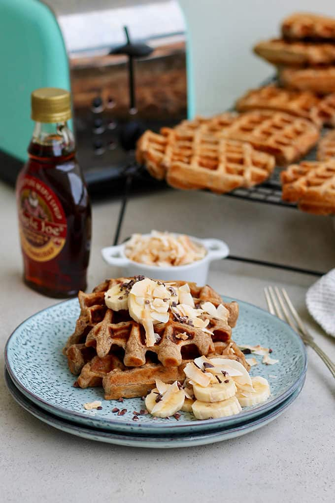 A plate of vegan banana waffles with a blue toasted in the background
