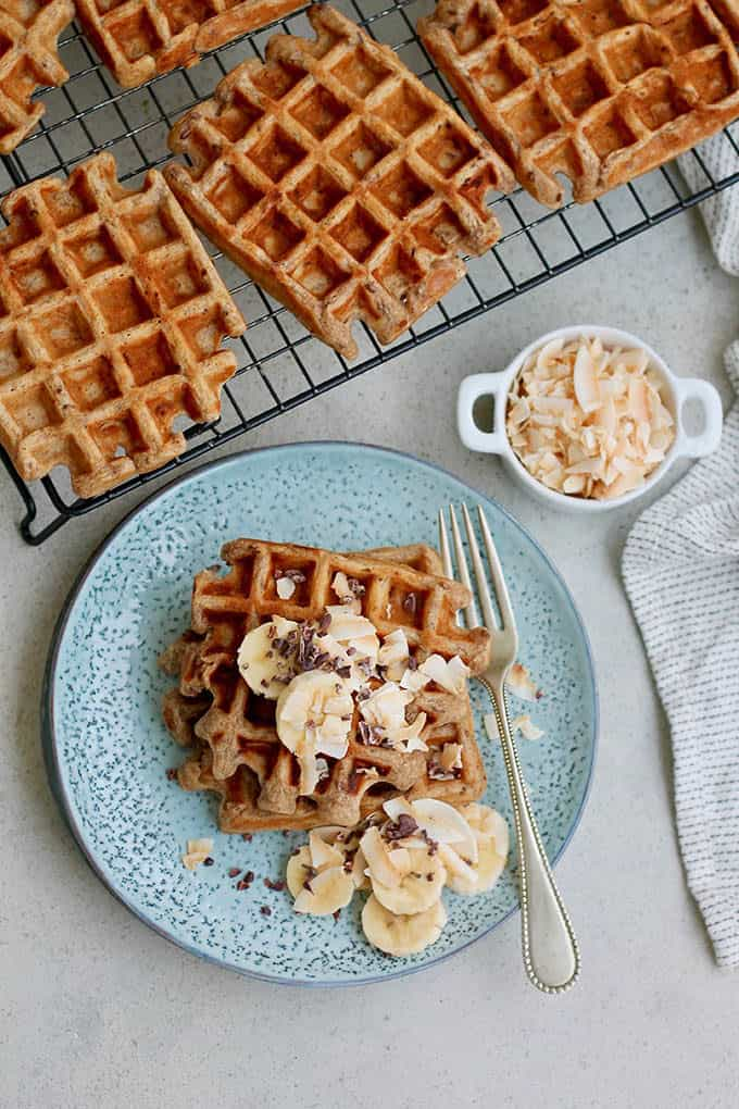 Overhead photo of vegan banana waffles on a blue plate topped with sliced banana, and a cooling rack of waffles to the side